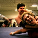 Two men in a wrestling mat on the ground wrestling