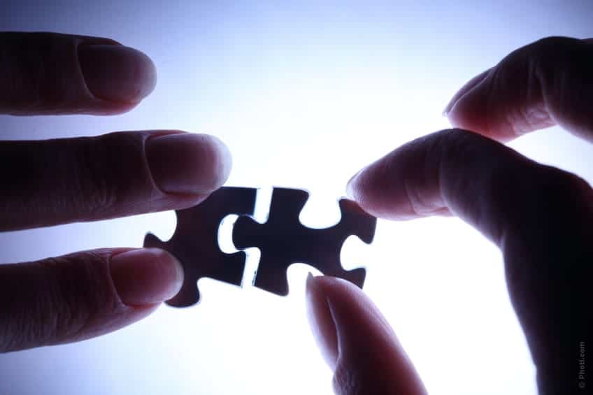 Hands putting two puzzles pieces together