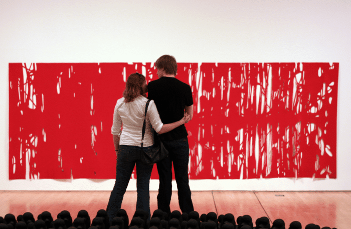 Two people standing in front of a large red painting at a museum