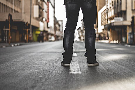 The back of the legs of a person wearing jeans standing in the middle of the street