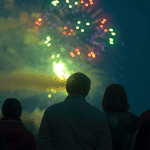 a silhouette of people watching fire works