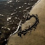 A heart drawn in the sand at the beach getting washed away