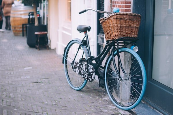 Blue bike with basket outside leaning against a wall