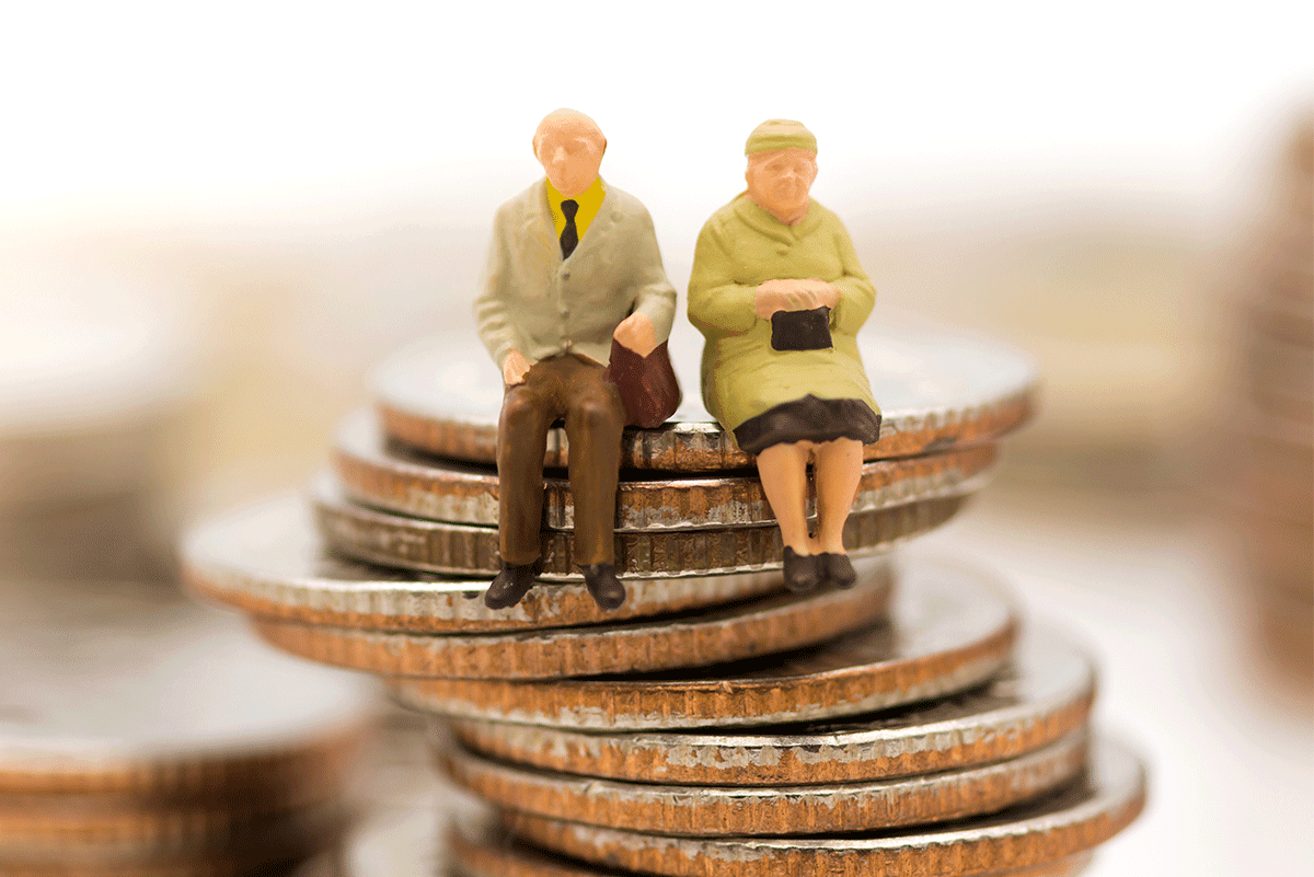 Toy figures of an old couple sitting on stacked coins