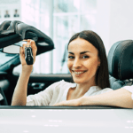 Smiling young women sitting on the driver sit holding the car key