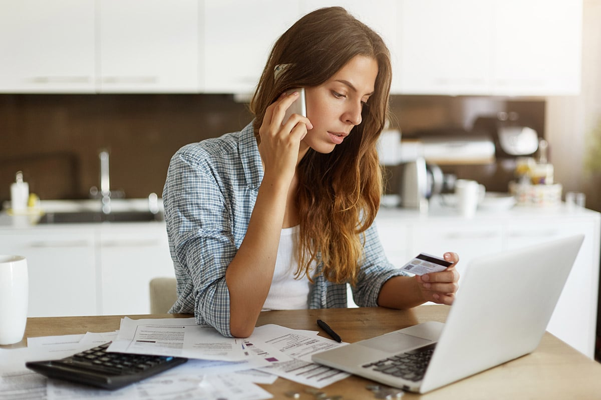 Young women sitting at a desk on her phone looking at a credit card