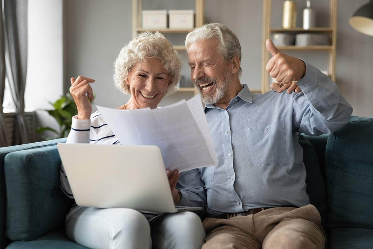 Old couple sitting on the couch happily looking at their paper