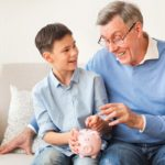 Boy And Elderly Grandfather Putting Coin Into Piggy Bank Talking About Value Of Money