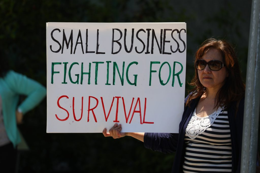 Business owner holding a sign