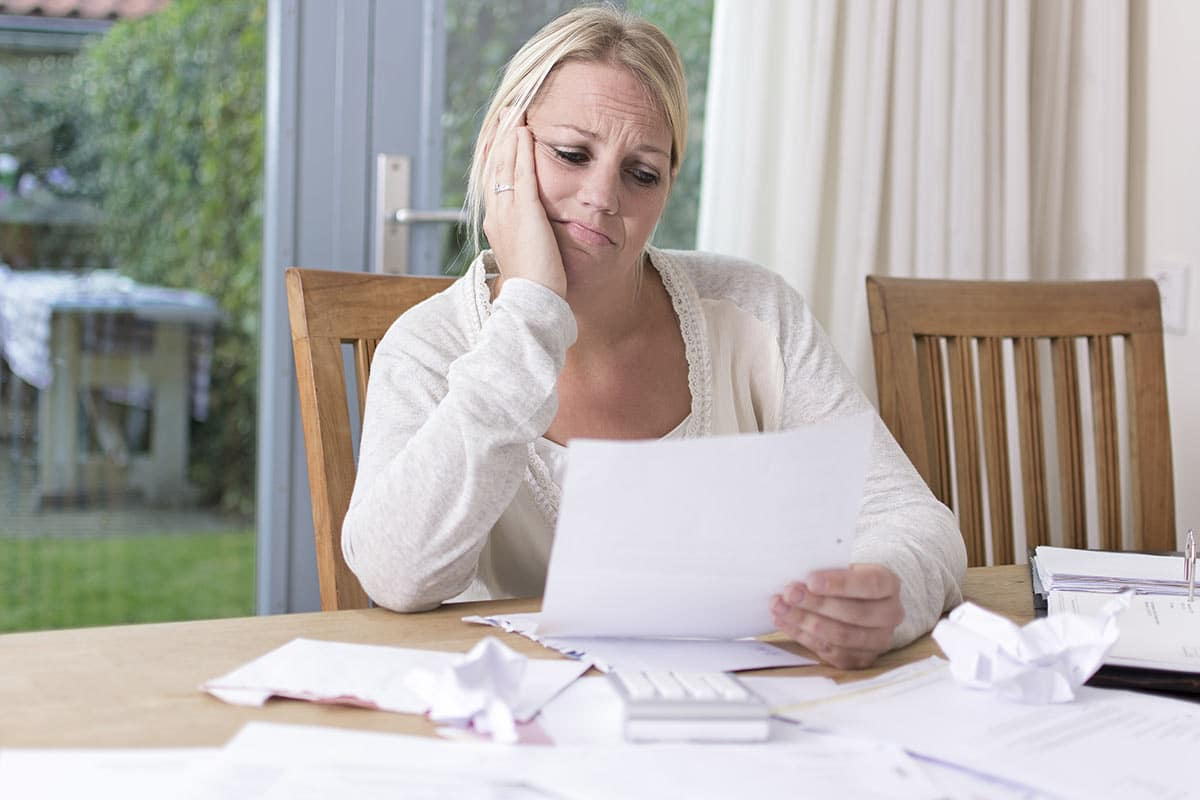 Woman looking at credit report how debt can affect mortgage