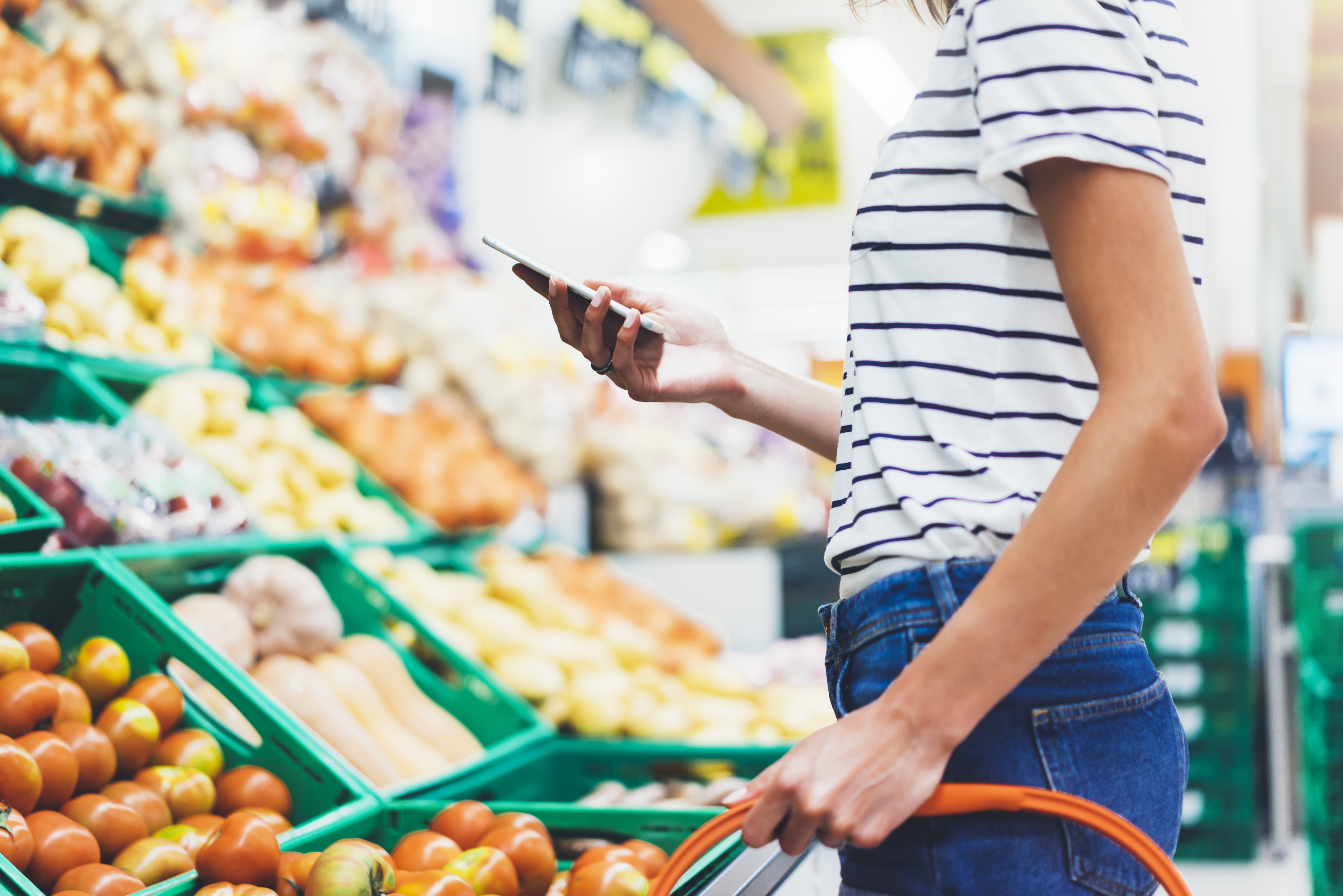 woman shopping and looking at food budget on phone